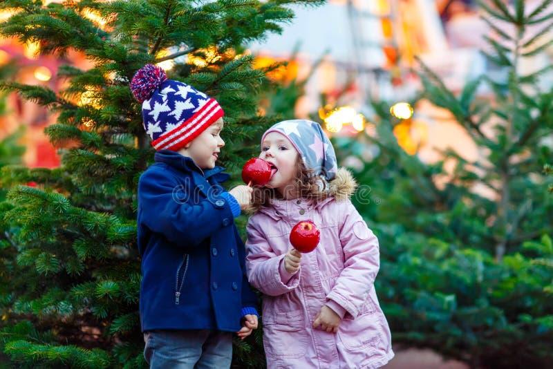 Twee het kleine jonge geitjes crystalized eten appel op Kerstmismarkt stock afbeeldingen