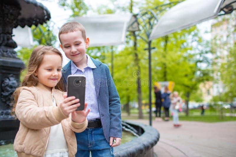 Twee het kleine jonge geitjes openlucht nemen selfie De pretconcept van de liefdevriendschap Kleine volwassenen royalty-vrije stock afbeeldingen