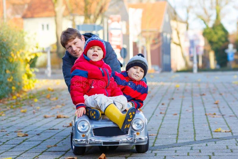 Twee het kleine van de jonge geitjesjongens en vader spelen met auto, in openlucht stock fotografie