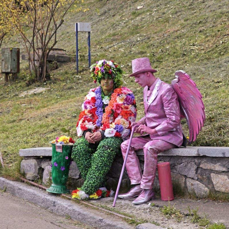 Twee het niet geïdentificeerde busking in kostuums nabootst ontspannen bij park in Kiev stock fotografie