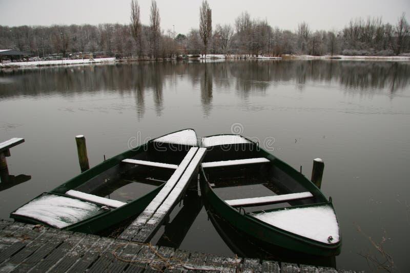 Twee het roeien boten die met sneeuw in de wintermeer worden behandeld royalty-vrije stock afbeelding