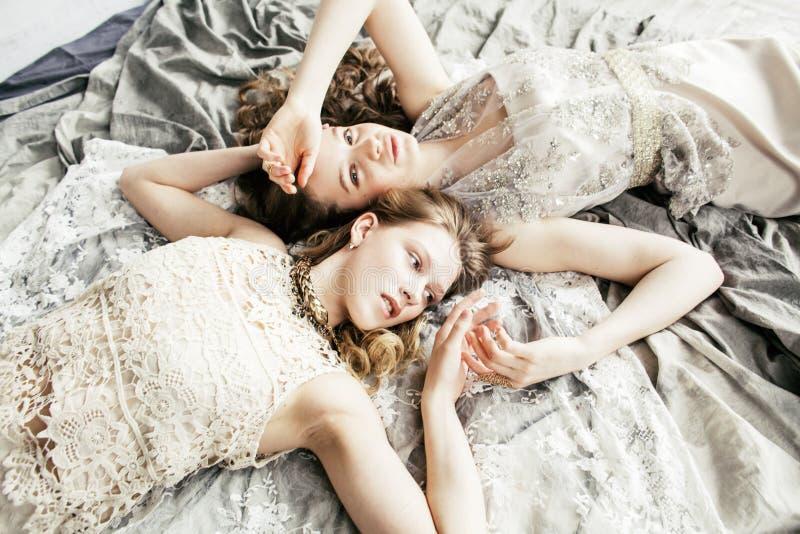 Twee het vrij tweelingmeisje van het zuster blonde krullende kapsel in het binnenland van het luxehuis samen, rijk jongerenconcep royalty-vrije stock afbeeldingen