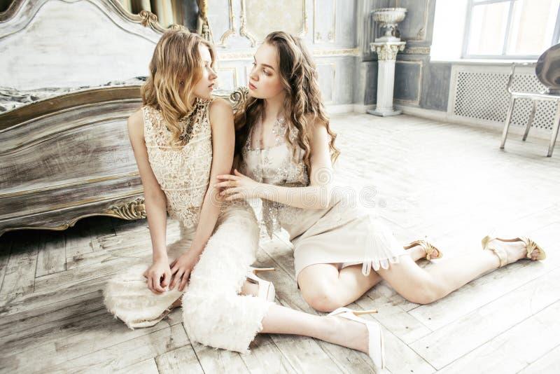 Twee het vrij tweelingmeisje van het zuster blonde krullende kapsel in het binnenland van het luxehuis samen, rijk jongerenconcep stock foto