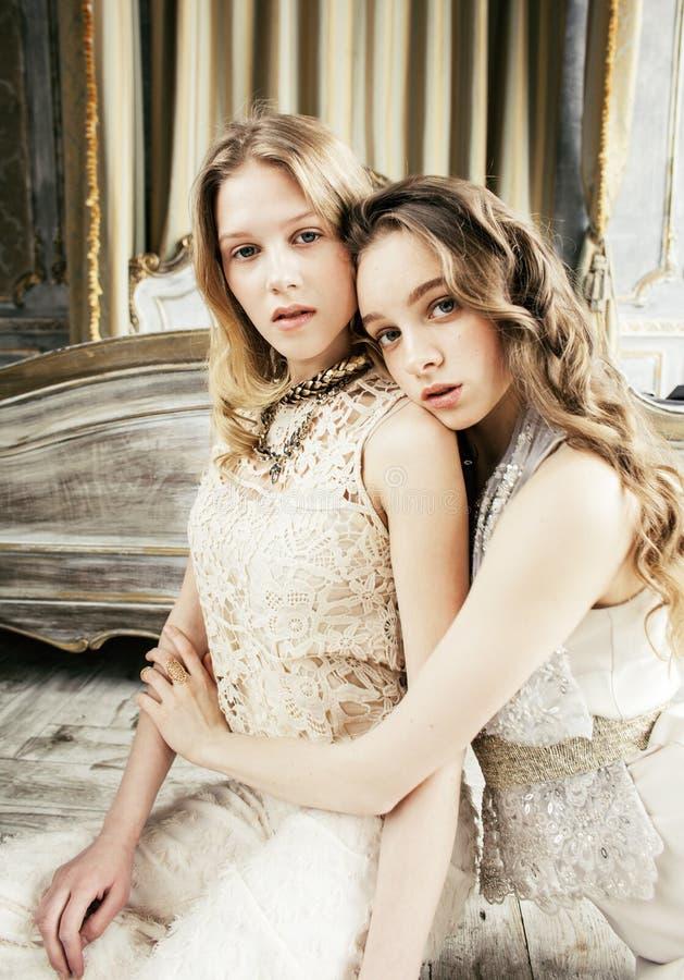 Twee het vrij tweelingmeisje van het zuster blonde krullende kapsel in het binnenland van het luxehuis samen, rijk jongerenconcep stock foto's
