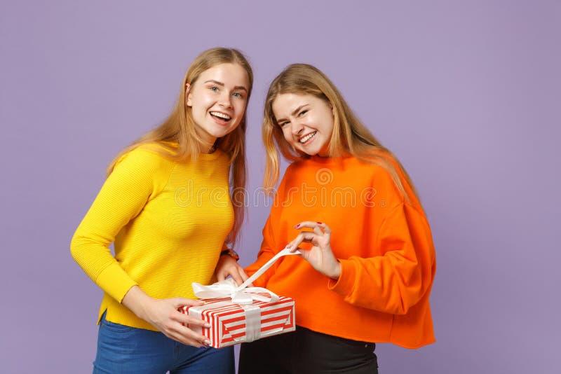 Twee het vrolijke blonde zustersmeisjes in levendige kleren samenbrengt houden rode gestreepte huidige doos met giftlint royalty-vrije stock afbeelding