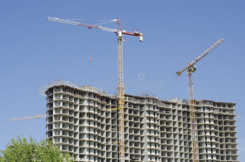 Twee high-rise multi-colored kranen naast het nieuwe gebouw in aanbouw royalty-vrije stock fotografie