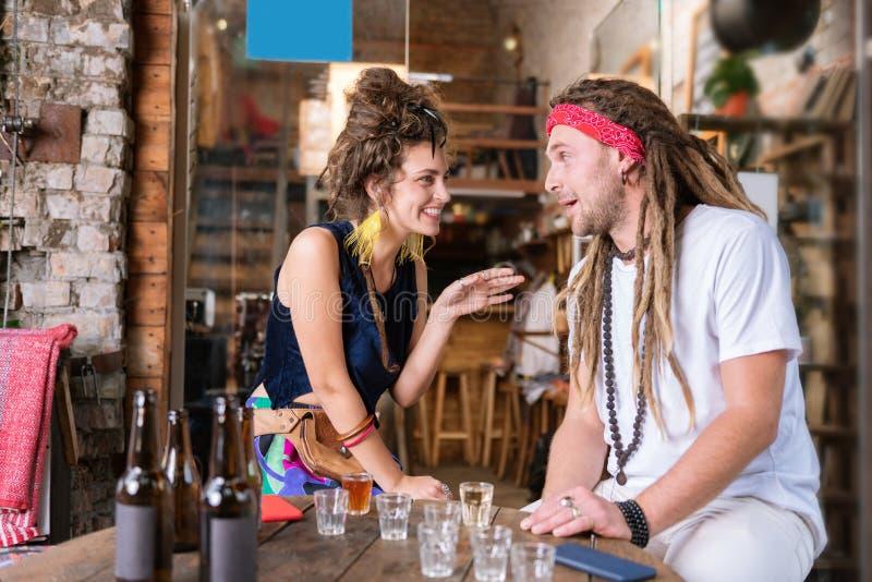Twee hippies die van hun mededeling in de bar genieten stock foto's