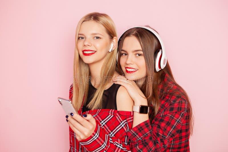 Twee hipstervrouw het stellen, het luisteren muziek door draadloze hoofdtelefoons en het maken selfie door smartphone op het roze stock fotografie