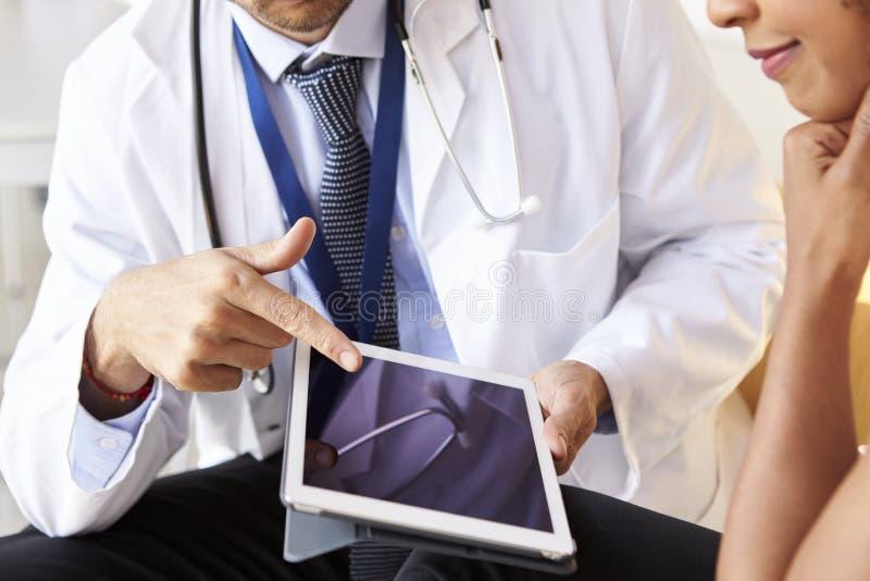 Twee hogere artsen die tabletcomputer, medio sectie met behulp van stock afbeelding