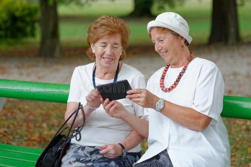 Twee hogere dames die nieuws op tablet lezen royalty-vrije stock afbeeldingen
