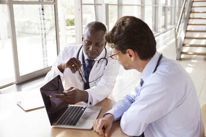 Twee hogere gezondheidszorgarbeiders in overleg die laptop met behulp van royalty-vrije stock foto