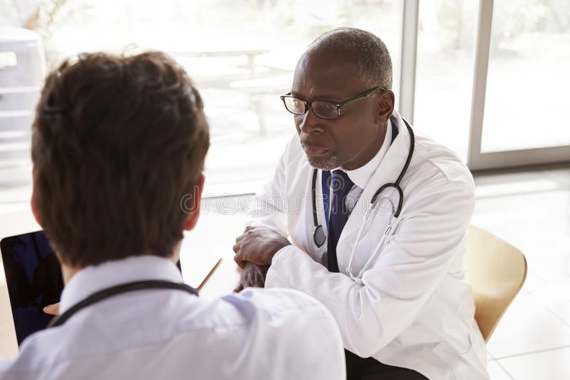Twee hogere gezondheidszorgarbeiders in overleg, over schouder stock afbeelding