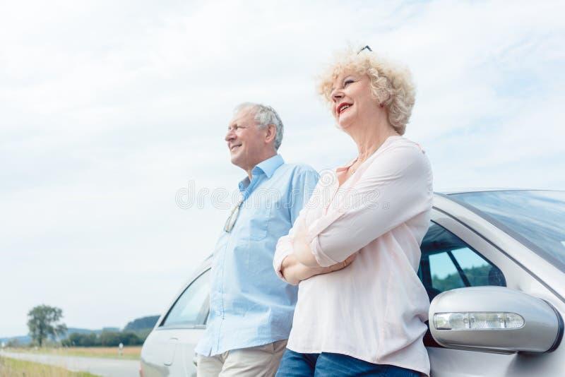 Twee hogere mensen die met vertrouwen glimlachen terwijl het leunen op hun stock foto's