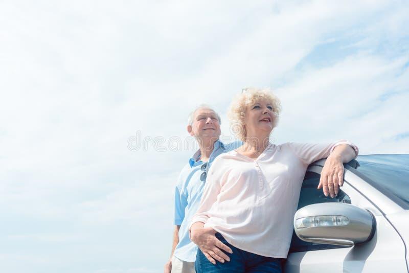 Twee hogere mensen die met vertrouwen glimlachen terwijl het leunen op hun royalty-vrije stock afbeeldingen