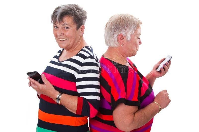 Twee hogere vrouwen die met cellphones communiceren royalty-vrije stock afbeelding