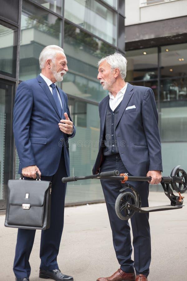 Twee hogere zakenlieden die voor een bureaugebouw spreken royalty-vrije stock foto's