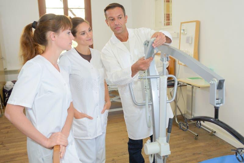 Twee homecareverpleegsters die leren hoe te hijstoestel te gebruiken royalty-vrije stock afbeeldingen