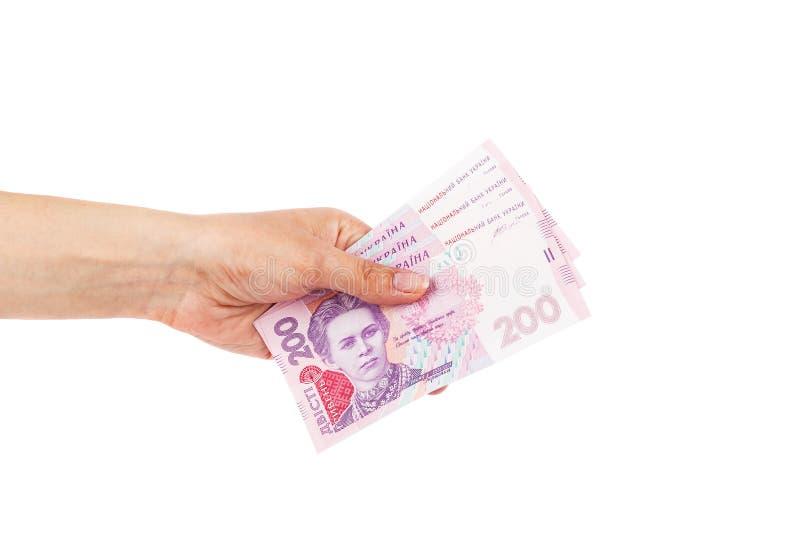 Twee honderd hryvnias in de geïsoleerde vrouwen` s hand, stock foto