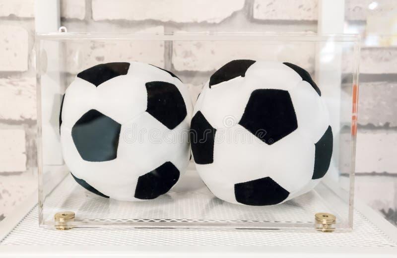 Twee hoofdkussens van het voetbalvoetbal in duidelijke acryldoos voor vertoning royalty-vrije stock fotografie