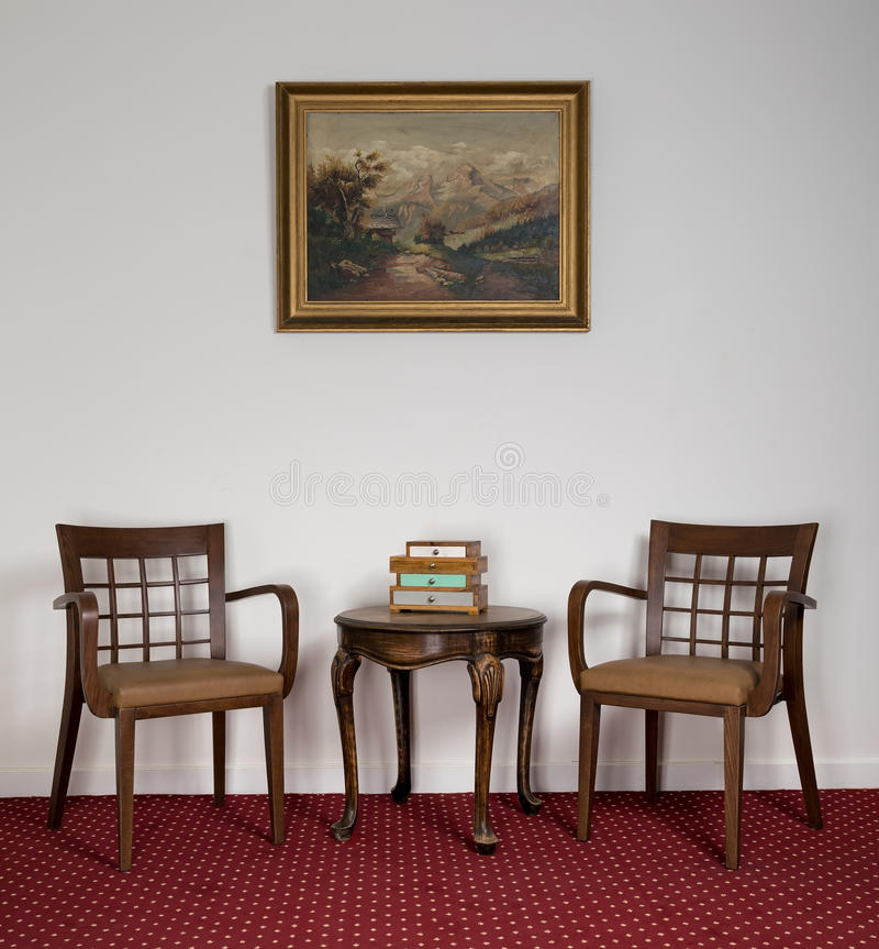 Twee houten leunstoelen, kleine ronde koffietafel en het ontworpen schilderen royalty-vrije stock afbeelding
