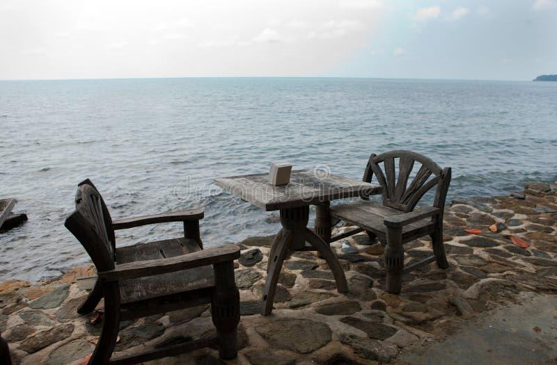 Twee houten stoelen op het strand stock foto's