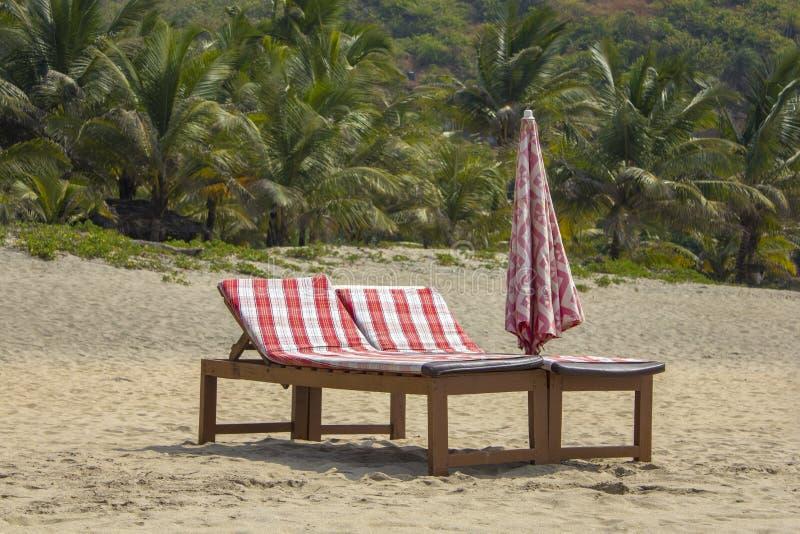 Twee houten strandbedden met rode matrassen en een gevouwen paraplu op het zand tegen de achtergrond van een onscherpe groene pal stock foto's