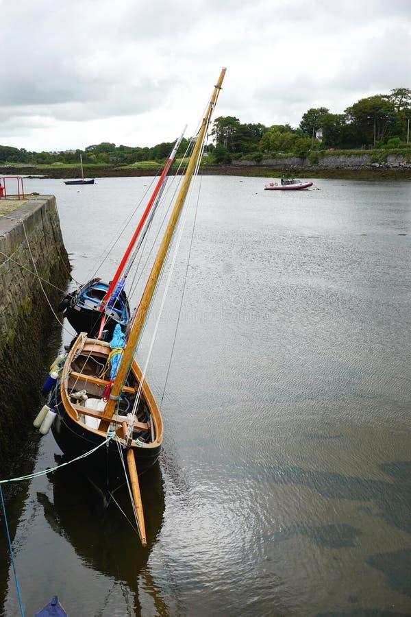 Twee houten zeilboten verankerden tegen een steenzeedijk in een beschermde haven in landelijk Ierland stock afbeeldingen