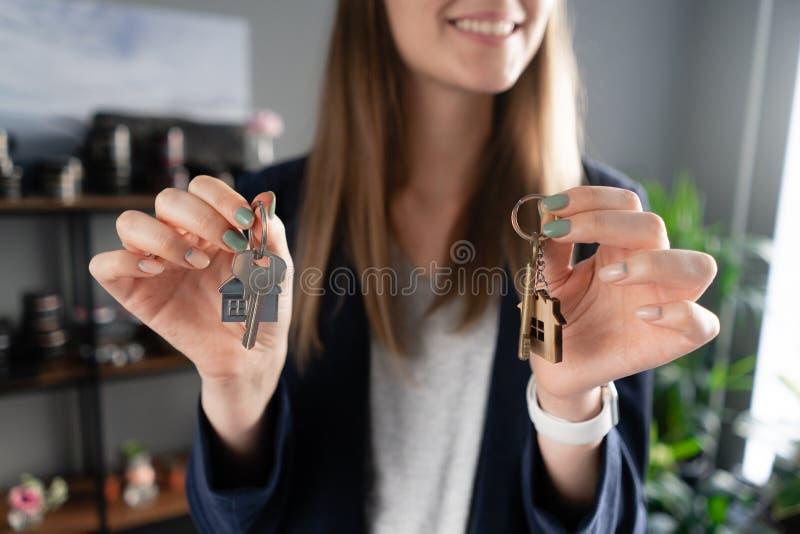 Twee huissleutels in de handen van de vrouw Jonge mooie vrouwenglimlachen Modern licht halbinnenland Onroerende goederen, hypothe stock foto