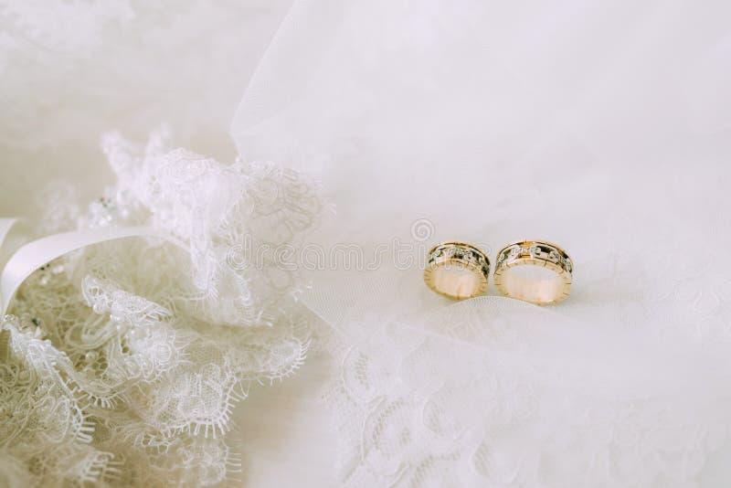 Twee huwelijks gouden ringen op mooi wit Tulle met kantkouseband sluiten royalty-vrije stock afbeelding