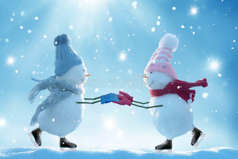 Twee ijs schaatsende sneeuwmannen stock afbeelding