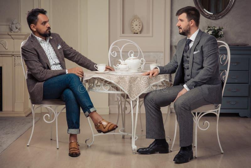 Twee imposimgmensen die bij de lijst converseren stock fotografie