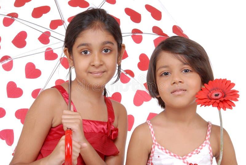Twee Indische zusters in rood en wit thema stock afbeeldingen