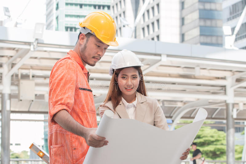 Twee ingenieurs die bij bouwwerf samenkomen Medewerkers het bespreken stock afbeelding