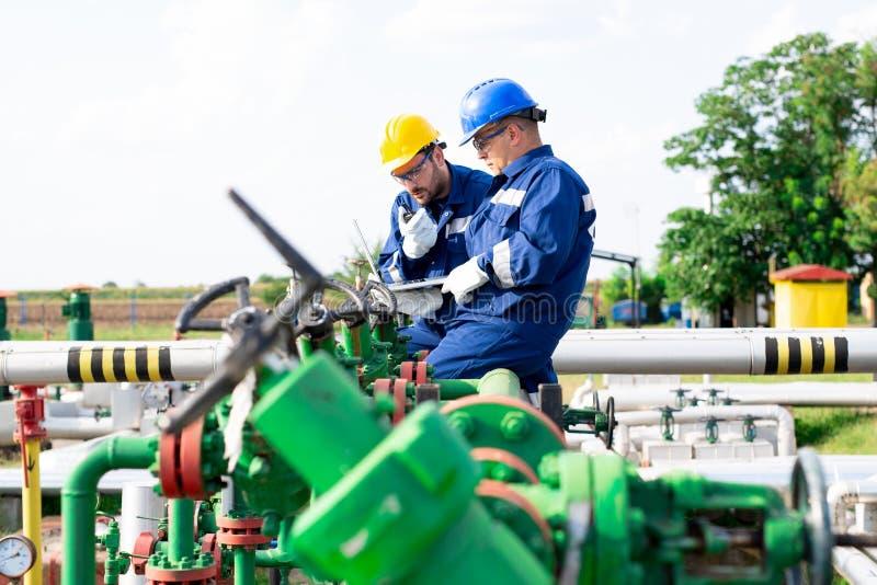 Twee ingenieurs die binnen olie en gasraffinaderij werken stock foto's