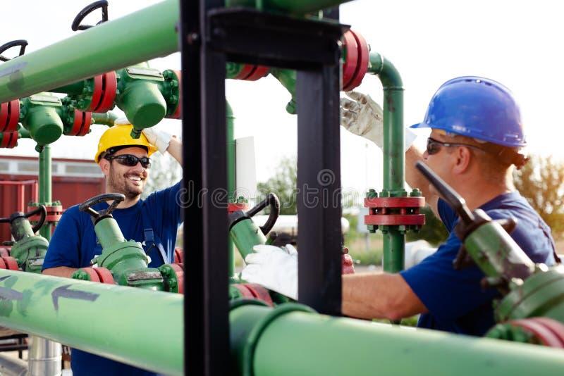 Twee ingenieurs die binnen olie en gasraffinaderij werken stock foto