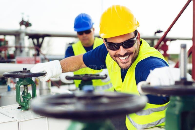Twee ingenieurs die binnen olie en gasraffinaderij werken stock afbeelding