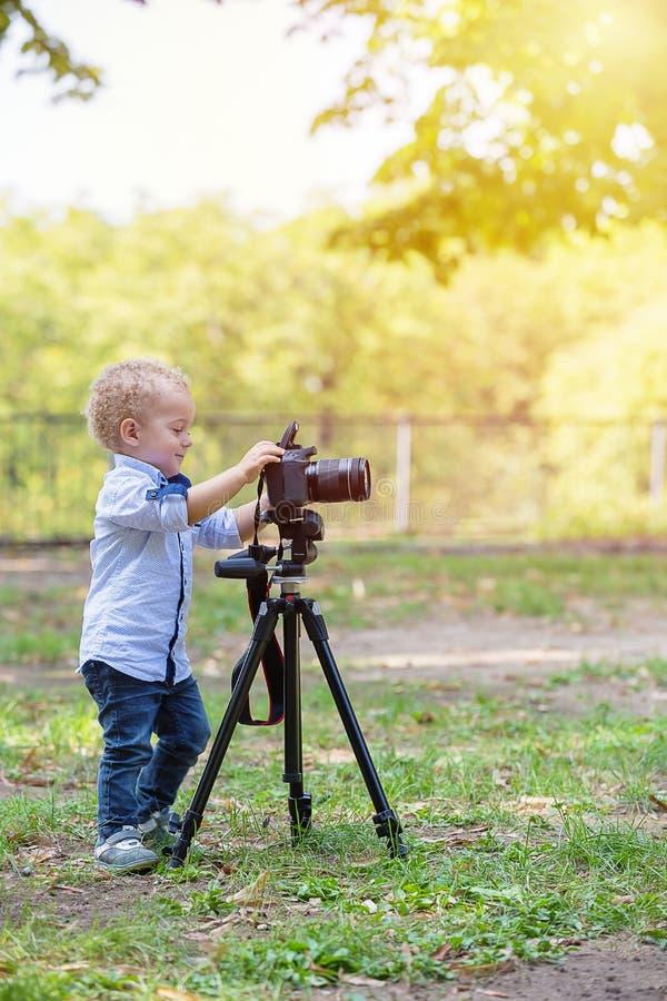 Twee jaar het oude jongen spelen met fotocamera stock foto