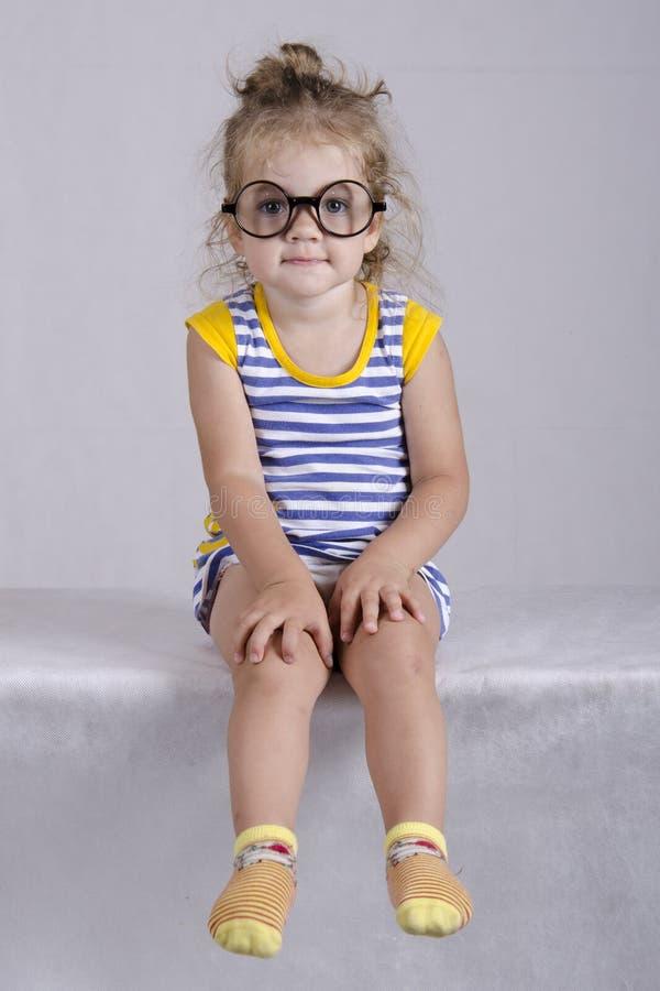 Twee-jaar-oud meisje in het grappige glazen zitten die in het kader kijken. Portret stock foto's