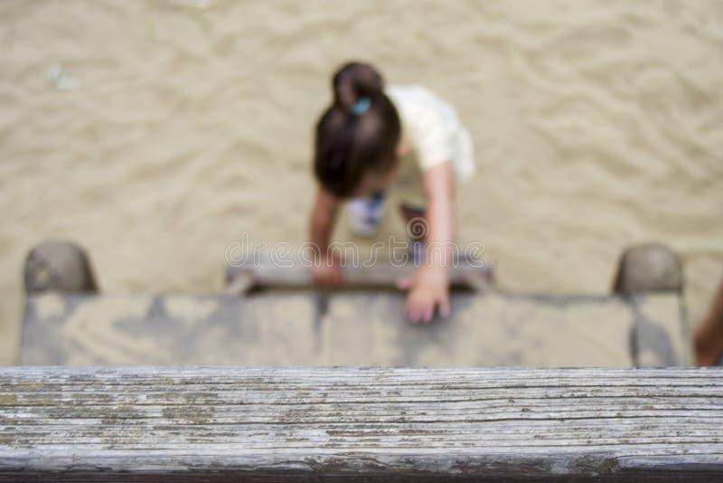 Twee jaar oud meisjes die op de ladder beklimmen stock foto