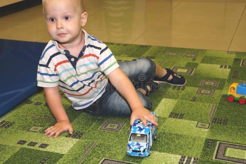 Twee jaar van de kindjongen het spel met auto's Onderwijsspeelgoed voor kleuterschool en kleuterschoolkind, binnenspeelplaats, le stock afbeelding