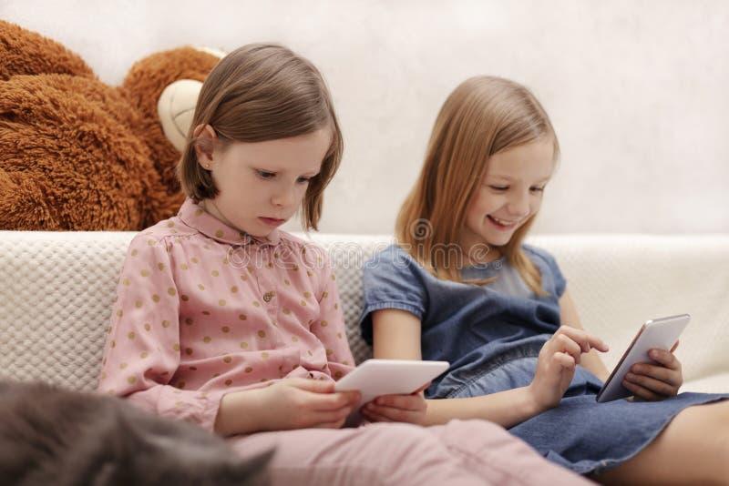 Twee jaar van meisjeszusters 7 en 8 oud letten op een e-book en op een smartphone thuis op de bank met hun kat stock afbeeldingen