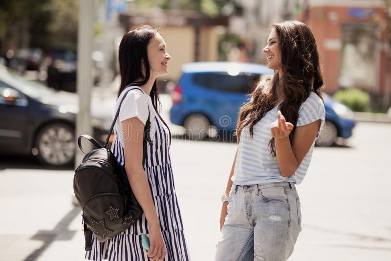 Twee jeugdige vrij slanke meisjes, die toevallige uitrusting dragen, bevinden zich bij de straat en het praatje stock foto
