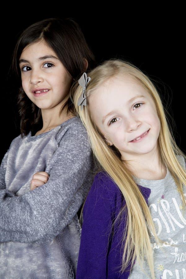 Twee jong meisjesportret die aanbiddelijk de camera bekijken stock fotografie