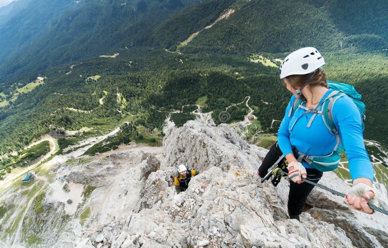Twee jonge aantrekkelijke alpinisten op zeer blootgesteld via Ferrata in het Dolomiet van Italië stock fotografie