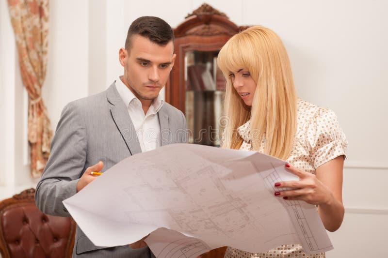 Twee jonge aantrekkelijke architecten die ontwerp bespreken stock afbeelding