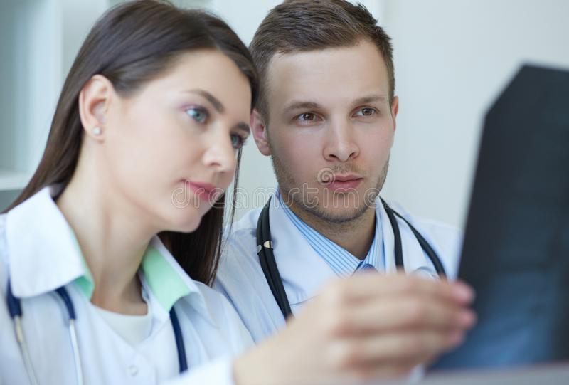 Twee jonge artsen als bekwame radiologen bespreken x-ray beeld diagnostiseren Radioloog of traumatologistconcept royalty-vrije stock afbeelding