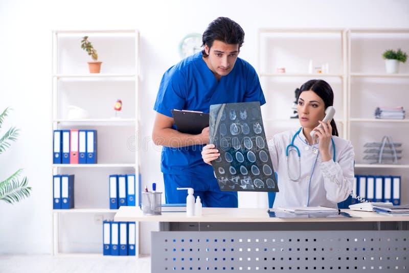Twee jonge artsen die in de kliniek werken stock foto
