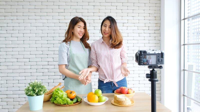 Twee jonge Aziatische bloggers die van het vrouwenvoedsel terwijl het registreren van video met gelukkig ogenblik, vlog concept,  stock afbeelding