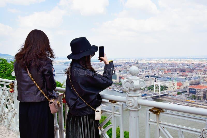 Twee jonge Aziatische vrouwen die beelden van de toneelmeningen van Boedapest nemen royalty-vrije stock afbeeldingen