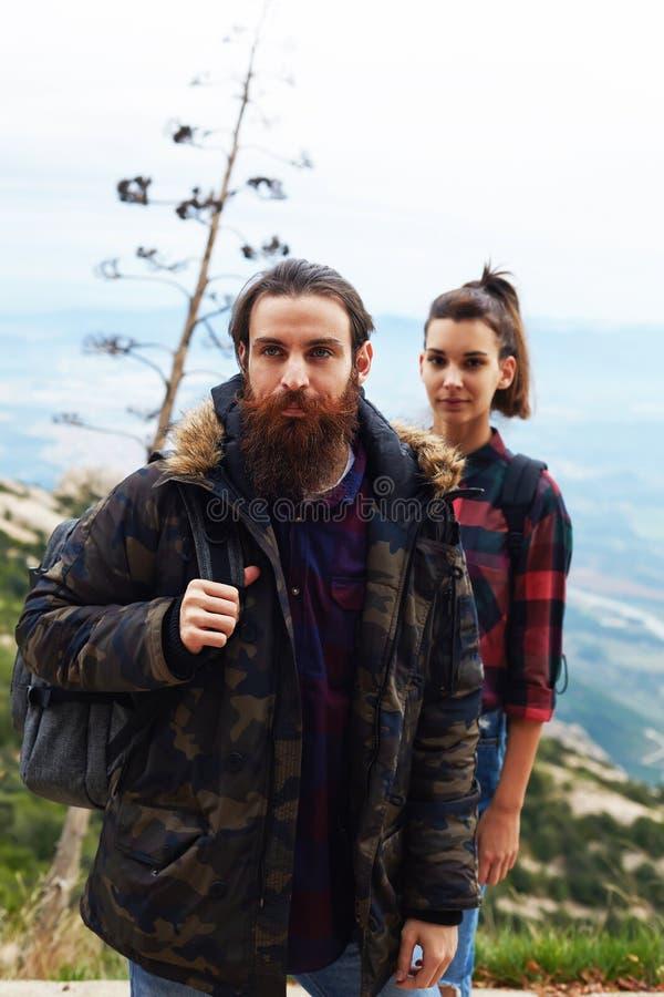 Twee jonge backpackers die in de bergen reizen stock afbeeldingen